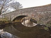 picture of old bridge  - Old arched stone bridge in english rural countryside setting over small stream - JPG