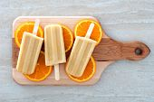 stock photo of flavor  - Frozen orange flavored yogurt pops with fruit slices on a wooden paddle board - JPG