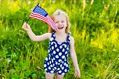 image of waving  - Laughing little girl with long curly blond hair holding american flag and waving it outdoor portrait on sunny day in summer park - JPG