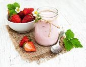 stock photo of yogurt  - Strawberry yogurt with fresh strawberries on a wooden background - JPG