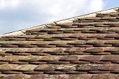 stock photo of red roof tile  - Old mossy tiled orange roof on a sunny day - JPG