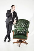 foto of prosperity  - Male businessman sitting on a green leather chair on a white background - JPG