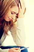 stock photo of pregnancy test  - Sad young woman holding pregnancy test feeling hopeless - JPG