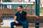 image of sitting a bench  - Handsome sexy and casual young man sitting on bench - JPG