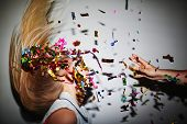 stock photo of confetti  - Blond girl dancing in nightclub while man throwing confetti at her - JPG