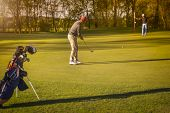 pic of golf bag  - Two male senior golf player putting on green at twilight - JPG