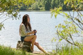 stock photo of takeaway  - Beautiful brunette teenage girl drinking takeaway coffee in park by the river on sunny summer day - JPG