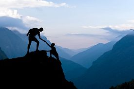 pic of leadership  - Teamwork couple helping hand trust assistance silhouette in mountains sunset - JPG