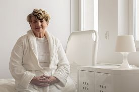 stock photo of hospital gown  - Senior woman wearing bathrobe in hospital room - JPG