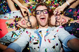 stock photo of selfie  - Cheerful friends lying on the floor in nightclub and making selfie - JPG