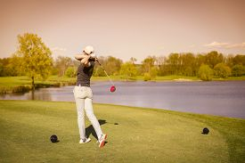 picture of swing  - Woman golf player swinging golf club from tee box at dusk - JPG