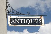 Old, rusty 'Antiques' wall sign on wrought iron bracket