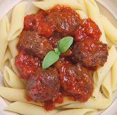 Meatballs in tomato sauce with rigatoni pasta.