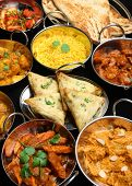 Indian food including curries, rice, samosas and naan bread.