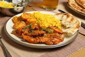 Indian chicken jalfrezi with potato curry, rice and naan bread.