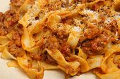 Tagliatelle pasta with bolognese sauce and grated Parmesan cheese.