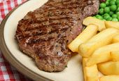 Chargrilled sirloin steak with chips and peas.