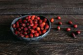 Постер, плакат: Rosehip Berries In A Clay Bowl