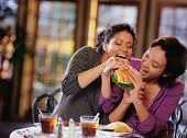 Young women fighting to take bite of hamburger