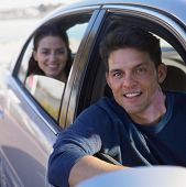 Young man driving a car with woman in backseat