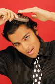 stock photo of close-up shot  - Portrait of businessman combing hair - JPG