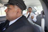Chauffeur and businessman in car