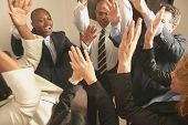 Business people cheering with hands raised