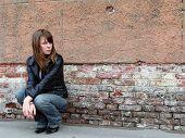 Girl Sitting Near Grunge Wall