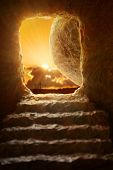 Open tomb of Jesus with sun appearing through entrance - Shallow depth of field on stone poster