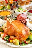 stock photo of turkey dinner  - Thanksgiving dinner with roast turkey baked ham pumpkin pie gravy dinner rolls cranberry chutney etc - JPG