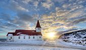 Typical red colored wooden church in Vik town, Iceland in winter. Sunrise light poster