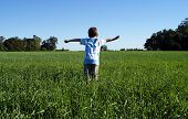 Boy Playing In A Wheat Field