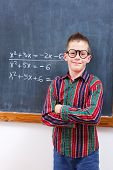 foto of eminent  - Eminent math boy in glasses standing in front of formulas - JPG