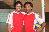 Team mates stood with volley ball on indoor court