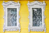 Two windows with carved wooden architraves