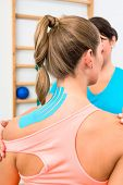 Woman from behind with Kinesio tape on shoulder during physiotherapy poster