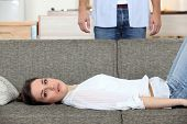 Woman laying on couch husband stood behind