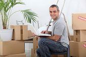 Man using a laptop computer sitting amongst cardboard boxes