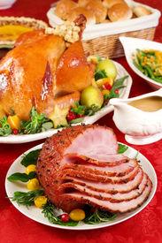 stock photo of christmas dinner  - Holiday dinner with baked ham roast turkey pumpkin pie gravy dinner rolls green beans salad - JPG