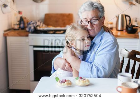 poster of Senior Woman Is Hugging Child In Cozy Kitchen At Home. Kid Is Enjoying Kindness, Warm Hands, Care, S