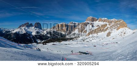 poster of Panorama of a ski resort piste with people skiing in Dolomites in Italy. Ski area Belvedere. Canazei