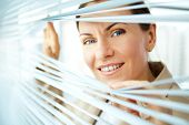 Confident business woman sliding apart blinds and looking at camera