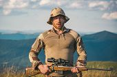 A Hunter With A Hunting Gun Hunt In Summer Forest. Mountain Hunting. Hunting Gear And Hunting Clothi poster