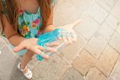 Childrens Hands Stretch Transparent Turquoise Slime. Against The Backdrop Of Venice Outside The Hous poster