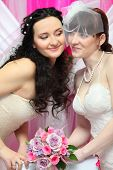 two happy brides look at each other and hold beautiful bouquet of roses; Focus on women on left