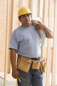 Construction worker carrying wiring on shoulder