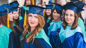 A Group Of Young Female Graduates. Female Graduate Is Smiling Against The Background Of University G poster