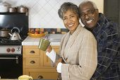 stock photo of mating  - Senior African couple hugging in kitchen - JPG