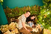 Portrait Of A Young Family Near The Christmas Tree. Happy Smiling Young Family Near The Christmas Tr poster