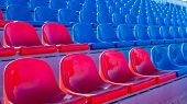 Bleachers In A Sports Stadium. Red And Blue Seats In A Large Street Stadium. poster